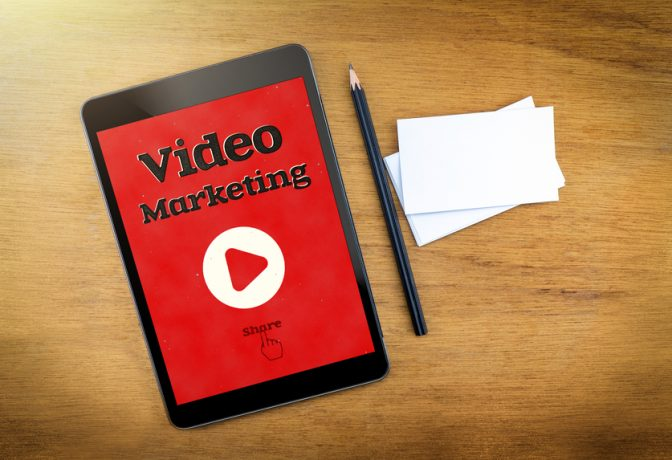 Video Marketing on mobile device screen with pen and business card on wood table,Digital marketing concept.