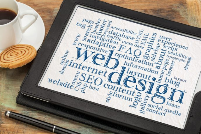 web or website design concept - a word cloud on a digital tablet with a cup of coffee