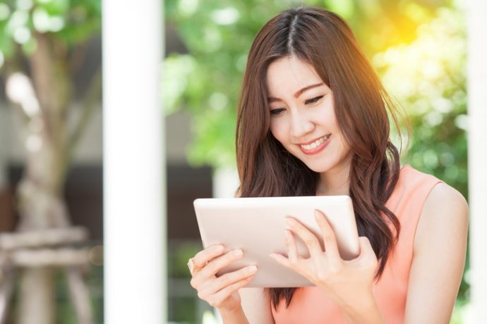 portrait of beautiful Asian woman use tablet in garden