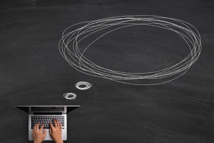 Online Communication concept with hands typing laptop on the blackboard background.