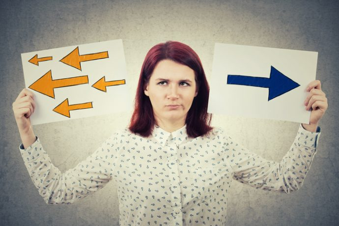 Confused young woman holding two papers in her hands with arrows poinded to the left and right side. Human emotion, face expression life perception concept. Business decision and choice symbol.